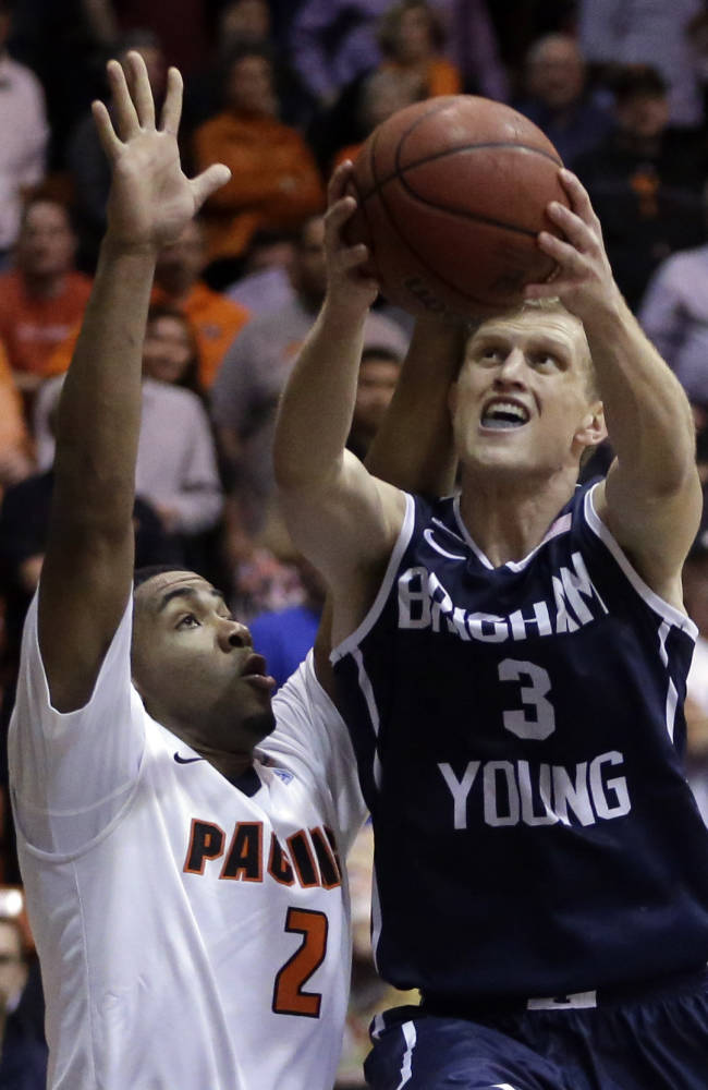 BYU's Tyler Haws, right, lays up a shot against Pacific's T.J. Wallace (2) in the second half of an NCAA college basketball game Thursday, Feb. 13, 2014, in Stockton, Calif
