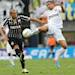 Santos' Bruno Peres, right, fights for the ball with Corinthians  Emerson during the final match of the Sao Paulo State soccer league in Santos, Brazil, Sunday, May 19, 2013