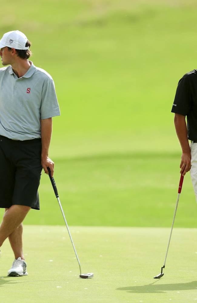 Stanford's Camerson Wilson, left, and Alabama's Bobby Wyatt look in different directions as they await their turn to putt on the sixth green during the second round of the NCAA college men's golf championship on Saturday, May 24, 2014, at Prairie Dunes Country Club in Hutchinson, Kan