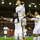 Swansea's Marvin Emnes, foreground left, celebrates with teammates after scoring against Liverpool, during the English League Cup soccer match between Liverpool and Swansea at Anfield Stadium, Liverpool, England, Tuesday Oct. 28, 2014
