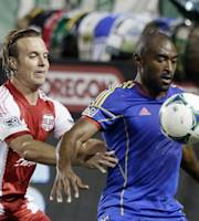 Colorado Rapids defender Marvell Wynne, right, holds off Portland Timbers defender Michael Harrington as he controls the ball during the first half of an MLS soccer game in Portland, Ore., Friday, Sept. 20, 2013.(AP Photo/Don Ryan)