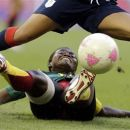 Cameroon's Francoise Bella tackles Britain's Alex Scott, during the women's group E soccer match between Great Britain and Cameroon, at the Millennium stadium in Cardiff, Wales, at the 2012 London Summer Olympics, Saturday, July 28, 2012. (AP Photo/Luca Bruno)