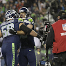 Seattle Seahawks' Zach Miller, second from right, is hugged by Seahawks' Breno Giacomini, left, after Miller scored a touchdown against the New Orleans Saints' in the first half of an NFL football game, Monday, Dec. 2, 2013, in Seattle The Associated Pre
