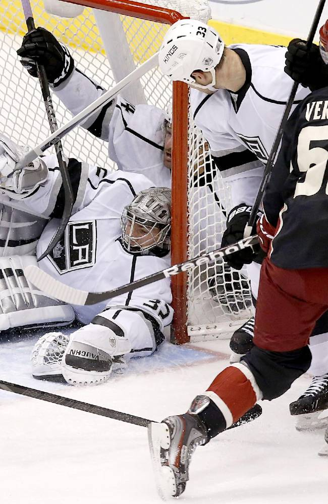 Phoenix Coyotes' Antoine Vermette (50) scores against Los Angeles Kings' Jonathan Quick (32) as Kings' Willie Mitchell (33) defends and Justin Williams, top left, collides with Quick inside the net during the third period of an NHL hockey game, Tuesday, Jan. 28, 2014, in Glendale, Ariz.  The Coyotes defeated the Kings 3-0