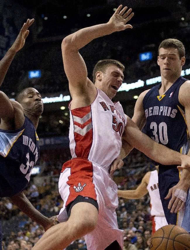 Toronto Raptors forward Tyler Hansbrough, center, is fouled as he battles with Memphis Grizzlies' Ed Davis, left, and Jon Leuer during the first half of a preseason NBA basketball game in Toronto on Wednesday, Oct. 23, 2013