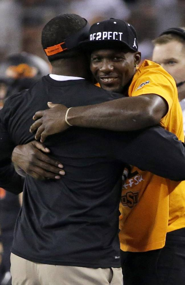 Dallas Cowboys' Dez Bryant, right, hugs a staff member on the Oklahoma State sideline during the first half of Oklahoma State's NCAA college football game against Florida State, Saturday, Aug. 30, 2014, in Arlington, Texas. Bryant played for OSU