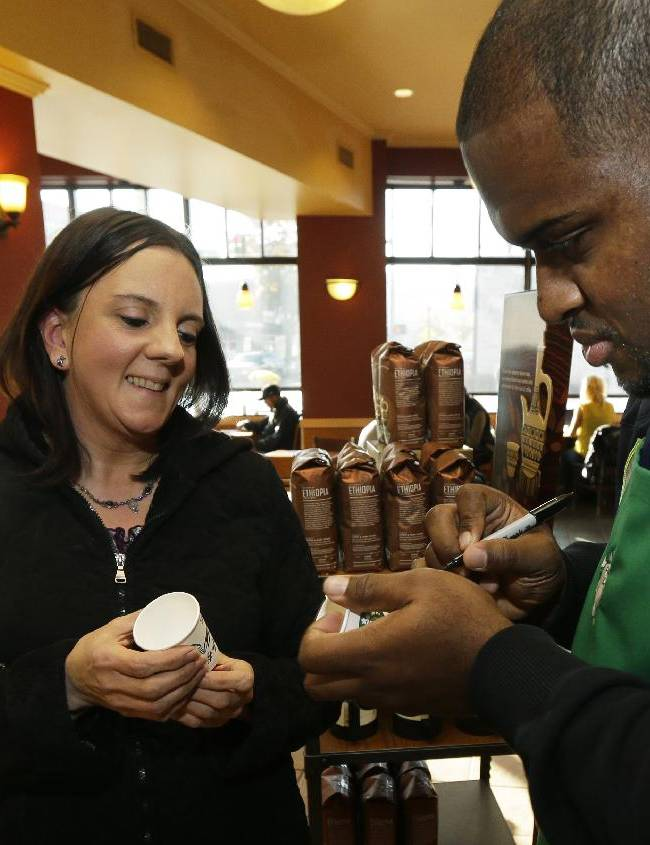 Seattle Seahawks NFL football defensive tackle Brandon Mebane, right, autographs a Starbucks paper cup for Diana Crosby, left, at a Seattle Starbucks store on Wednesday, Oct. 23, 2013, in Seattle. The Seahawks began a one-week fund-raising campaign Wednesday with Starbucks to benefit Seahawks head coach Pete Carroll's A Better Seattle program, which seeks to reach at-risk youth and prevent gang violence