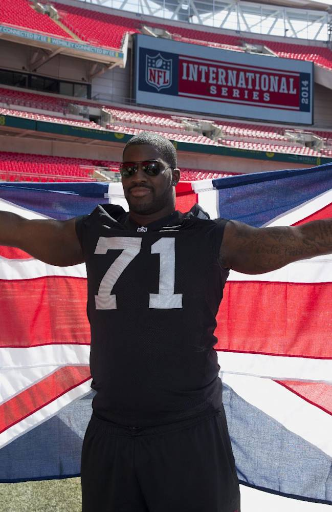NFL player British-born Oakland Raiders offensive tackle Menelik Watson poses for photographers with a Union flag at Wembley Stadium in London, Wednesday, July 16, 2014.  Six players from teams who will play in the three regular season NFL games at Wembley in the autumn were in London for media and promotional events on Wednesday