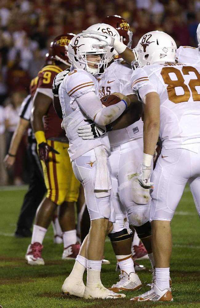 Texas quarterback Case McCoy, center, celebrates with teammates after scoring a touchdown during the second half of an NCAA college football game against Iowa State, Thursday, Oct. 3, 2013, in Ames, Iowa. Texas won 31-30