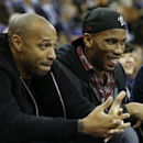 Chelsea soccer player Didier Drogba, right, and former Arsenal soccer player Thierry Henry watch during the NBA basketball game between Milwaukee Bucks and New York Knicks at the O2 Arena in London, Thursday, Jan. 15, 2015
