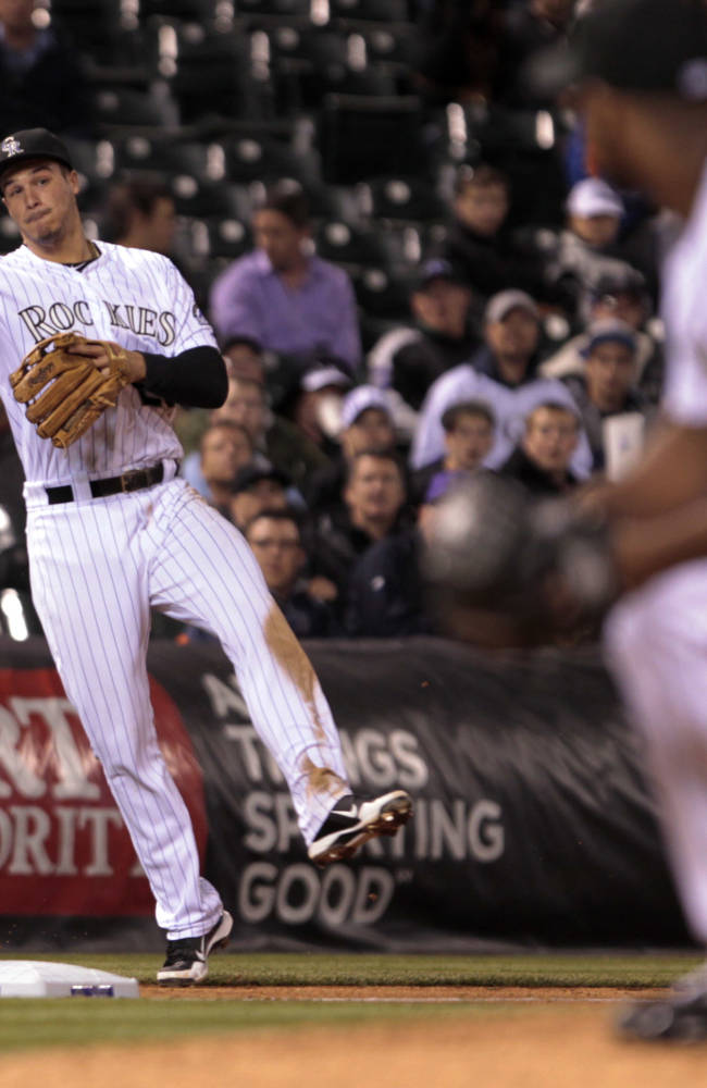 Colorado Rockies third baseman Nolan Arenado, left, throws to first base to put out New York Mets' David Right (not shown) at first base in the seventh inning of a baseball game in Denver, Thursday, May 1, 2014