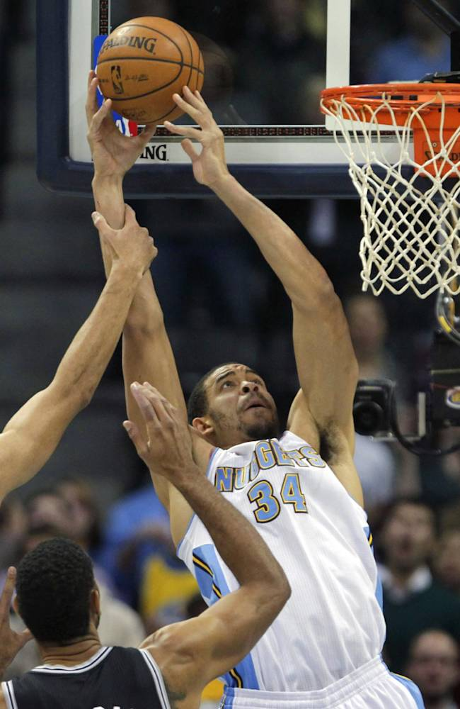 San Antonio Spurs guard Danny Green (4) fouls Denver Nuggets center JaVale McGee (34) in the first quarter of a basketball game in Denver on Tuesday, Nov. 5, 2013