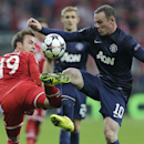 Bayern's Mario Goetze, left, is challenged by Manchester United's Wayne Rooney during the Champions League quarterfinal second leg soccer match between Bayern Munich and Manchester United in the Allianz Arena in Munich, Germany, Wednesday, April 9, 2014
