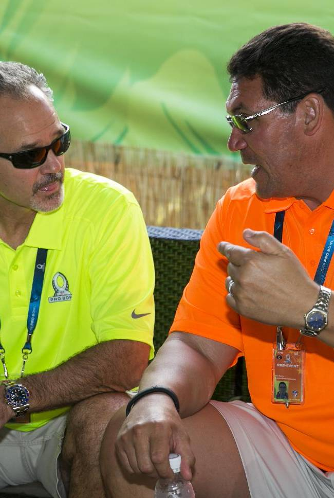 Indianapolis Colts coach Chuck Pagano, left, coach of Team Sanders in the NFL football Pro Bowl, chats with Carolina Panthers coach Ron Rivera, coach of Team Rice, in the green room during the second day of the draft for the game, Wednesday, Jan. 22, 2014, in Kapolei, Hawaii