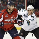 San Jose Sharks defenseman Scott Hannan (27) fights for position against Washington Capitals right wing Troy Brouwer (20) during the second period of an NHL hockey game, Tuesday, Oct. 14, 2014, in Washington. This was Hannan's 1,000th NHL hockey game The