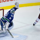 Arizona Coyotes' Martin Hanzal, right, of the Czech Republic, tips the puck past Vancouver Canucks' goalie Ryan Miller for his second goal during the second period of an NHL hockey game in Vancouver, British Columbia, on Friday Nov. 14, 2014 The Associate
