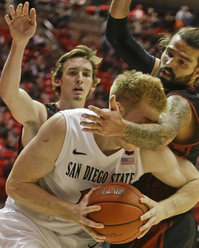 San Diego State forward James Johnson, front, is fouled by Saint Katherine's Joshua White, right, during the first half of an NCAA college basketball game on Friday Dec. 27, 2013, in San Diego