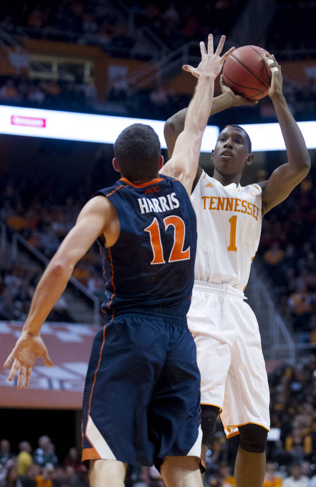 Tennessee's Josh Richardson (1) shoots while defended by Virginia's Joe Harris during an NCAA college basketball game at Thompson-Boling Arena on Monday, Dec. 30, 2013. Richardson totaled 20 points including four from the three-point line. Tennessee won 87-52