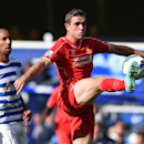 Liverpool's Jordan Henderson, right, competes for the ball with Queens Park Rangers' Carl Henry during their English Premier League soccer match at Loftus Road, London, Sunday, Oct. 19, 2014