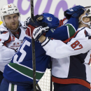 Vancouver Canucks' Brad Richardson, center, roughs up Washington Capitals' Liam O'Brien, right, as Karl Alzner tries to pull him away during the second period of an NHL hockey game in Vancouver, British Columbia, on Sunday, Oct. 26, 2014 The Associated Pr