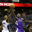 Sacramento Kings' Tyreke Evans (13) shoots in front of Orlando Magic's E'Twaun Moore (55) during the first half of an NBA basketball game, Wednesday, Feb. 27, 2013, in Orlando, Fla. (AP Photo/John Raoux)