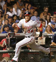 Washington Nationals' Bryce Harper heads home scoring on a single by Ian Desmond during the ninth inning of a baseball game against the Chicago Cubs Tuesday, Aug. 20, 2013, in Chicago. The Nationals won 4-2. (AP Photo/Charles Rex Arbogast)