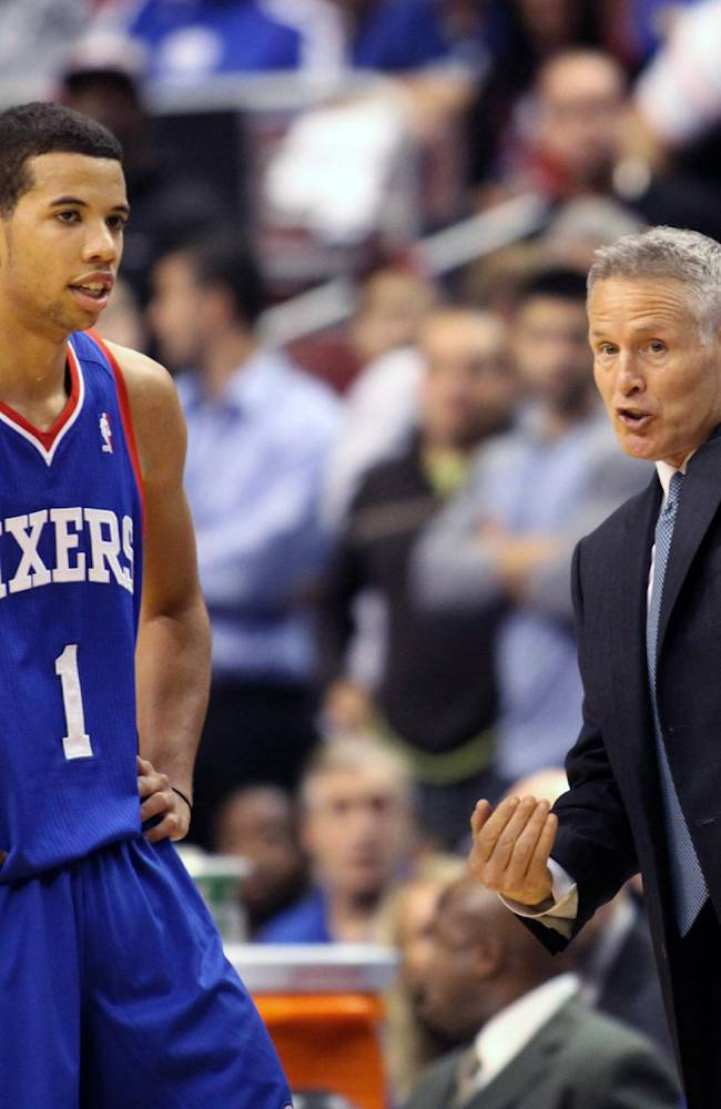 Philadelphia 76ers coach Brett Brown speaks to Michael Carter-Williams (1) as they play the Chicago Bulls in the second  half of an NBA basketball game Saturday Nov. 2, 2013, in Philadelphia. The 76ers won 107-104