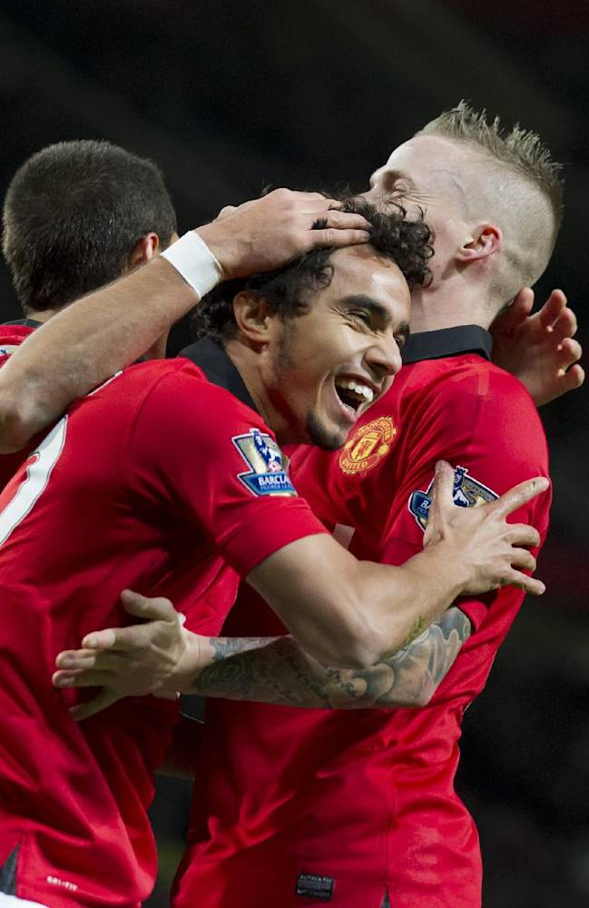 Manchester United's Fabio celebrates with teammates after scoring against Norwich, during their English League Cup soccer match at Old Trafford Stadium, Manchester, England, Tuesday Oct. 29 , 2013