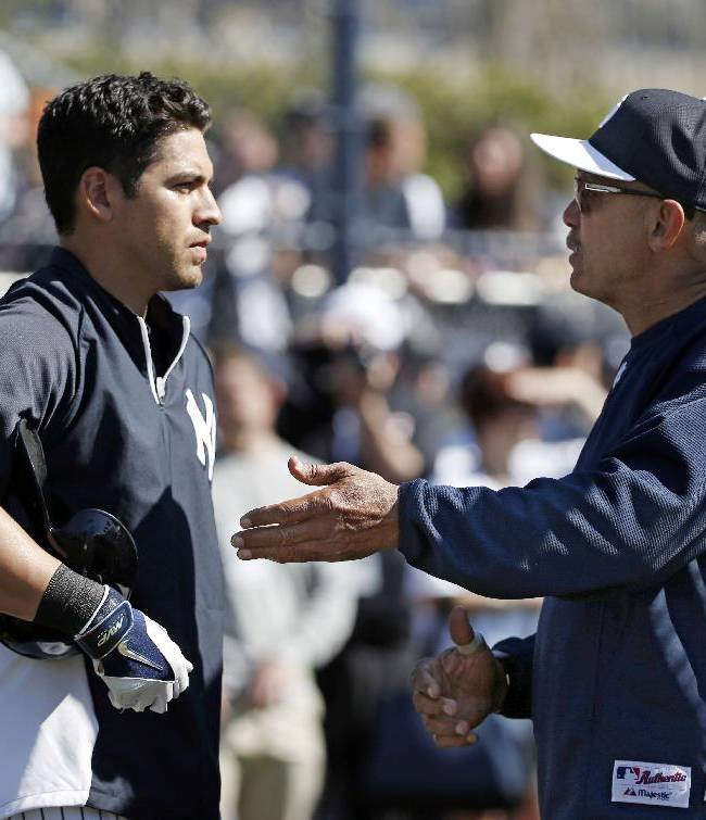 New York Yankees Jacoby Ellsbury, left, listens to Yankees special adviser Reggie Jackson before taking batting practice prior to a spring training baseball game against the Tampa Bay Rays in Tampa, Fla., Sunday, March 9, 2014