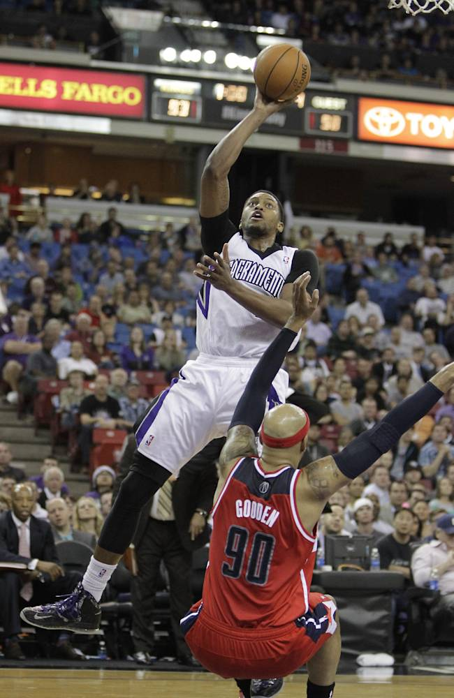 Sacramento Kings forward Rudy Gay, left, goes to the basket against Washington Wizards forward Drew Gooden during the fourth quarter of an NBA basketball game in Sacramento, Calif., Tuesday, March 18, 2014.  The Kings won in overtime 117-111