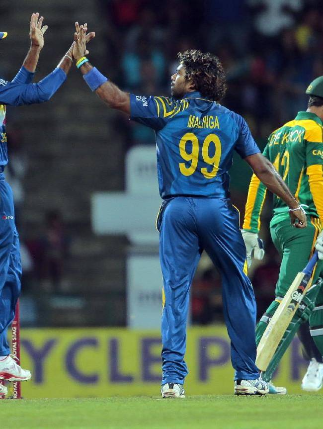 Sri Lankan bowler Lasith Malinga, center, celebrates with a teammate the dismissal of South African batsman Quinton de Kock during the second one-day international cricket match between Sri Lanka and South Africa in Pallekele, Sri Lanka, Wednesday, July 9, 2014