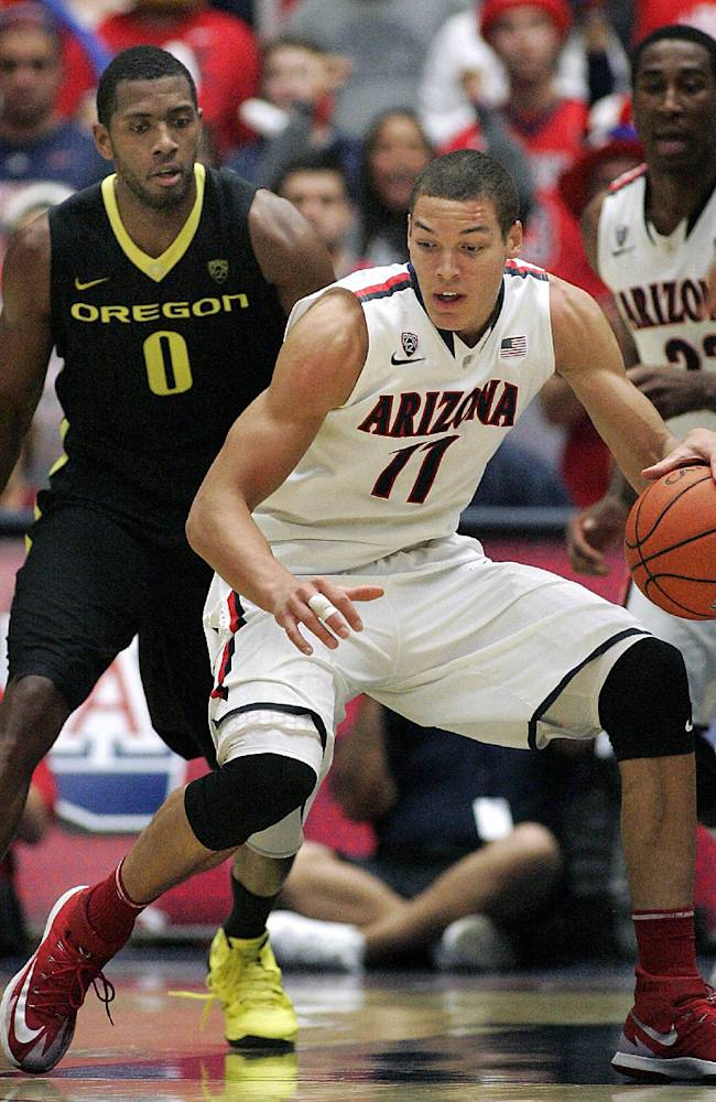 Arizona's Aaron Gordon (11) recovers a loose ball in front of Oregon's Mike Moser (0) in the second half of an NCAA college basketball game on Thursday, Feb. 6, 2014 in Tucson, Ariz. Arizona won 67 - 65