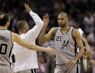 San Antonio Spurs' Tim Duncan celebrates with the team as he comes down to the bench during the overtime in Game 2 of the Western Conference finals NBA basketball playoff series against the Memphis Grizzlies, Tuesday, May 21, 2013, in San Antonio. San Antonio won 93-89. (AP Photo/Eric Gay)