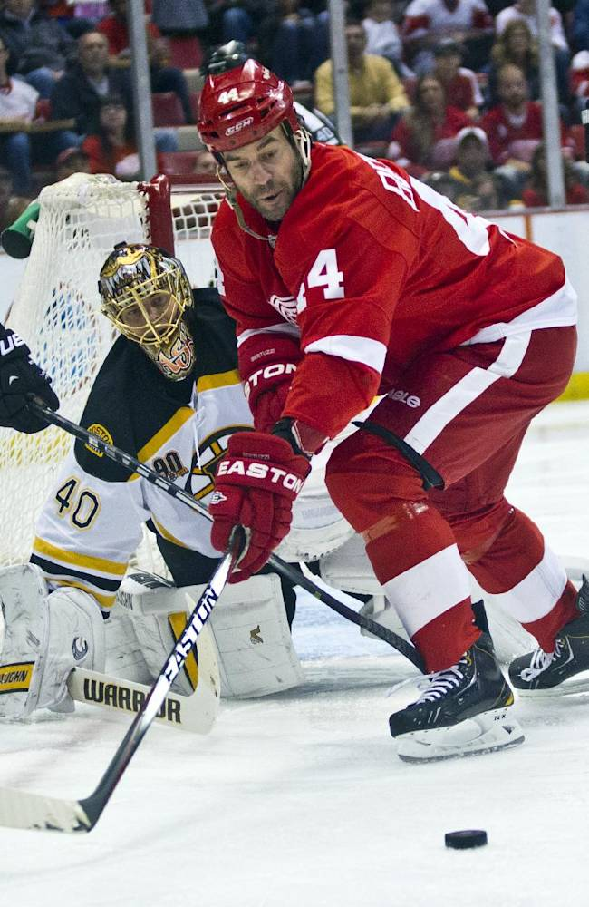 Detroit Red Wings forward Todd Bertuzzi (44) reaches for the puck in front of Boston Bruins goalie Tuukka Rask (40), of Finland, during the second period of an NHL hockey game in Detroit, Mich., Wednesday, April 2, 2014