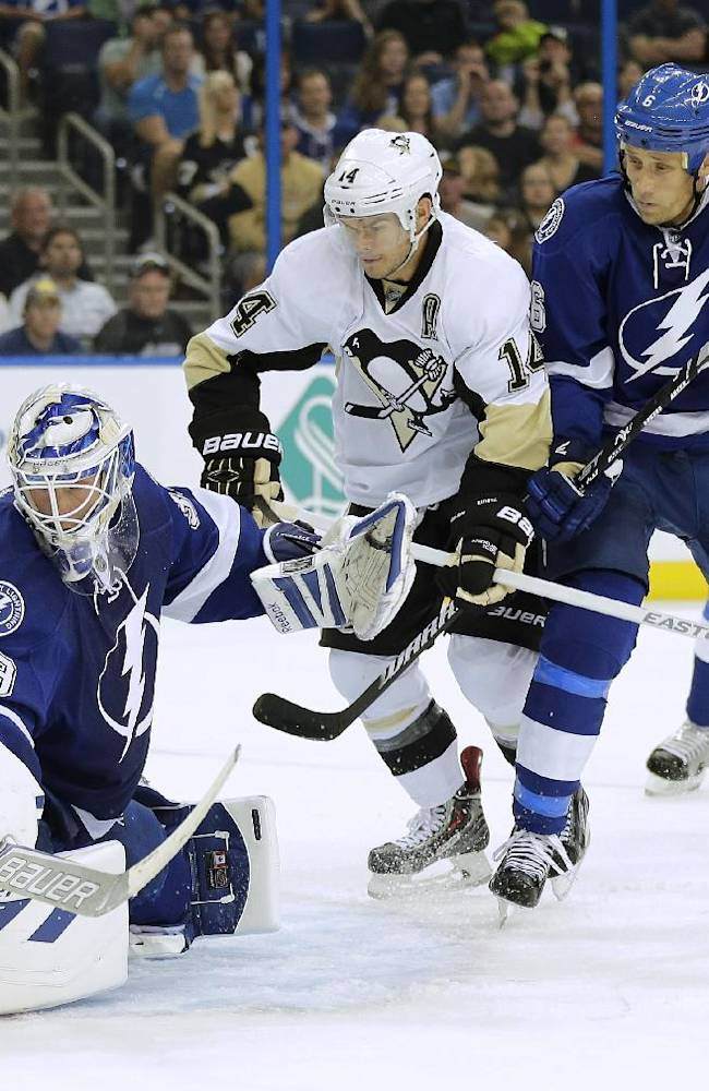 Tampa Bay Lightning goalie Anders Lindback (39), of Sweden, makes a save on a shot by Pittsburgh Penguins left wing Chris Kunitz (14) as Lightning defenders Sami Salo (6), of Finland, and Victor Hedman look on during the first period of an NHL hockey game on Saturday, Oct. 12, 2013, in Tampa, Fla