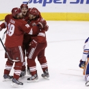 Phoenix Coyotes' Oliver Ekman-Larsson, second from left, of Sweden, celebrates his goal with teammates Shane Doan, left, and Antoine Vermette as Edmonton Oilers' Justin Schultz (19) kneels on the ice during the second period of an NHL hockey game, Friday,