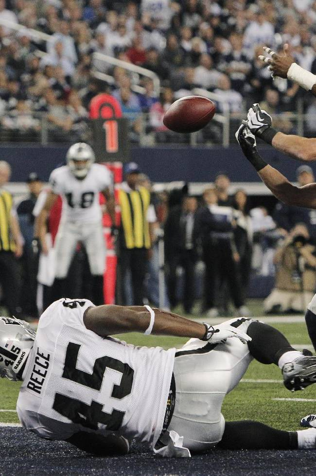 Dallas Cowboys strong safety Jeff Heath and J.J. Wilcox (27) try for a loos ball against Oakland Raiders fullback Marcel Reece (45) during the second half of an NFL football game, Thursday, Nov. 28, 2013, in Arlington, Texas