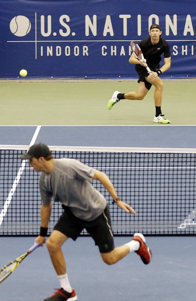Bob Bryan, foreground, hits a return to Eric Butorac in the doubles finals at the U.S. National Indoor Tennis Championships, Sunday, Feb. 16, 2014, in Memphis, Tenn. The team of Raven Klaasen and Butorac won 6-4, 6-4