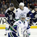Vancouver Canucks goalie Ryan Miller (30) stops a shot in front of teammate Christopher Tanev (8) and Columbus Blue Jackets' Nick Foligno (71) during the second period of an NHL hockey game in Columbus, Ohio, Friday, Nov. 28, 2014 The Associated Press