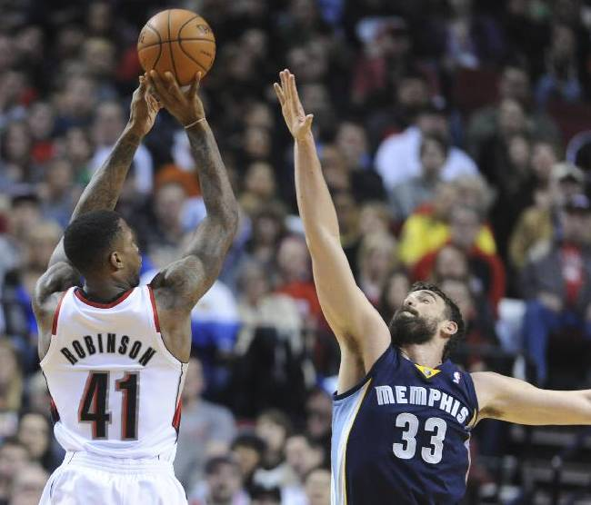 Memphis Grizzlies' Marc Gasol (33) defends a shot by Portland Trail Blazers' Thomas Robinson (41) during the first half of an NBA basketball game in Portland, Ore., Sunday March 30, 2014