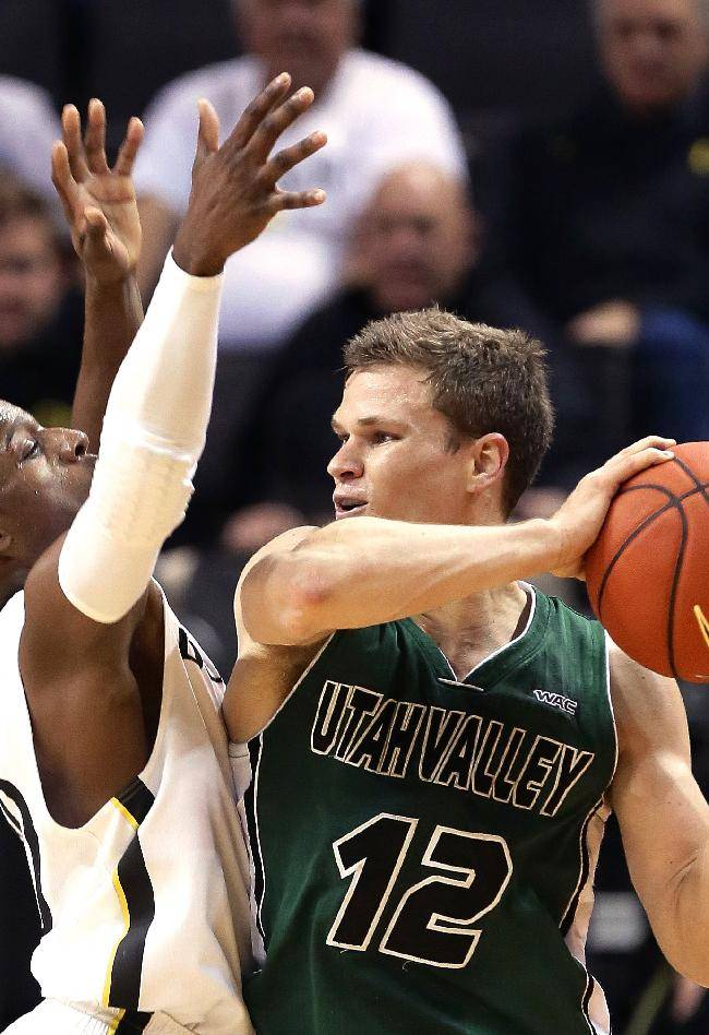 Utah Valley guard Holton Hunsaker, right, looks to pass against Oregon guard Johnathan Loyd during the first half of an NCAA college basketball game in Eugene, Ore., Tuesday, Nov. 19, 2013