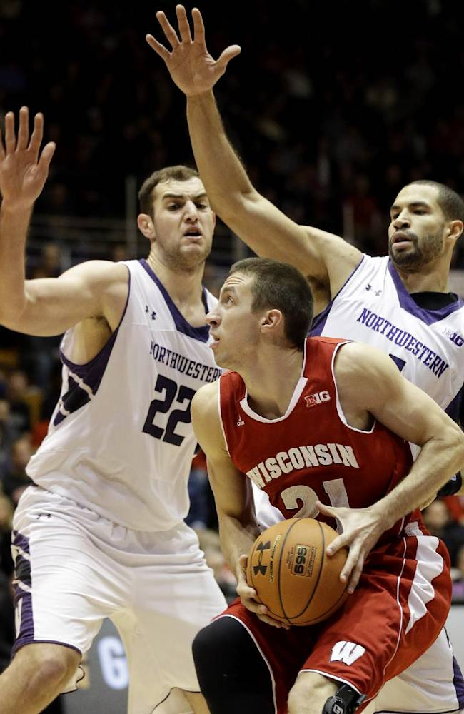 Wisconsin's Josh Gasser (21) looks to the basket as Northwestern center Alex Olah (22) and guard Drew Crawford, left, defend during the first half of an NCAA college basketball game in Evanston, Ill., on Thursday, Jan. 2, 2014