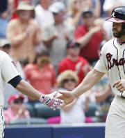 Atlanta Braves' Evan Gattis (24) celebrates with teammate Chris Johnson after hitting a solo home run in the fourth inning of a baseball game against the Chicago Cubs, Sunday, May 11, 2014, in Atlanta. (AP Photo/John Bazemore)