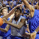 White squad's Archie Goodwin, center, puts up a shot between Blue squad's Jarrod Polson, left, and Willie Cauley-Stein (15) during Kentucky's NCAA college basketball Blue-White scrimmage at Rupp Arena in Lexington, Ky., Wednesday, Oct. 24, 2012. (AP Photo/James Crisp)