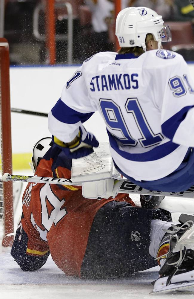 Tampa Bay Lightning center Steven Stamkos (91) collides with Florida Panthers goalie Tim Thomas (34) after scoring a goal in the first period during a preseason NHL hockey game, Saturday, Sept. 28, 2013, in Sunrise, Fla