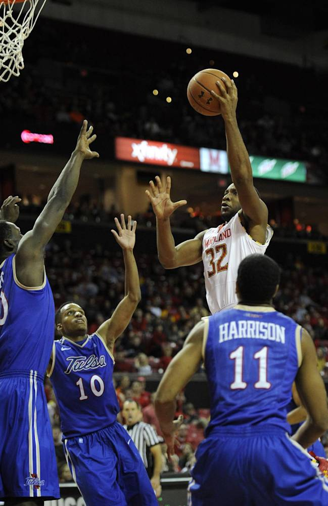 Maryland's Dez Wells (32) goes to the basket against Tulsa guard Shaquille Harrison (11), James Woodard (10) and D'Andre Wright, left, during the second half of an NCAA college basketball game, Sunday, Dec. 29, 2013, in College Park, Md. Maryland won 85-74