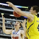 Michigan's Mitch McGary (4) knocks the ball away from Florida's Erik Murphy (33) during the first half of a regional final game in the NCAA college basketball tournament, Sunday, March 31, 2013, in Arlington, Texas. (AP Photo/David J. Phillip)