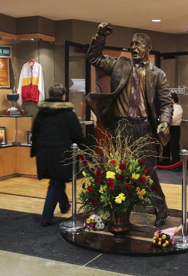 Fans pass by a statue of former Iowa State basketball coach Johnny Orr before Iowa State's NCAA college basketball game against Northern Illinois at Hilton Coliseum in Ames, Iowa, Tuesday, Dec. 31, 2013. Orr, 86, who also coached at Michigan, has died, Iowa State confirmed Tuesday