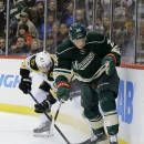 Minnesota Wild defenseman Jonas Brodin, right, and Boston Bruins left wing Brad Marchand, left, chase the puck during the second period of an NHL hockey game in St. Paul, Minn., Wednesday, Dec. 17, 2014. (AP Photo/Ann Heisenfelt)