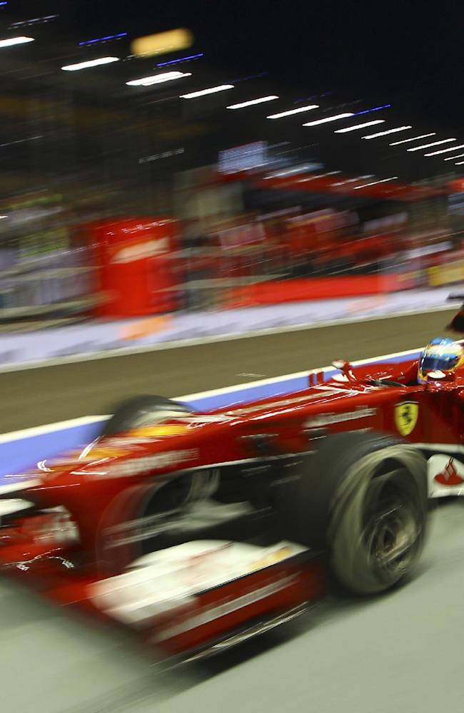 Ferrari driver Fernando Alonso of Spain steers his car into the pit lane during the first practice session for the Singapore Formula One Grand Prix on the Marina Bay City Circuit in Singapore, Friday, Sept. 20, 2013